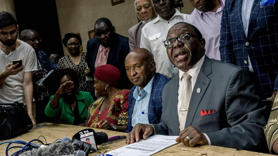 "ZANU-PF spokesperson Simon Khama Moyo (R) reads the outcome of the caucus meeting on November 20, 2017 at party headquarters in Harare. Impeachment would be an ignominious end to the career of the ""Grand Old Man"" of African politics, once lauded as an anti-colonial hero and the only leader Zimbabwe has known since it gained independence from Britain in 1980. (Zinyange Auntony / AFP)"
