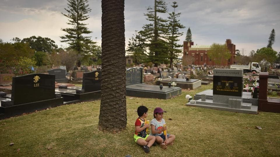 Visitors sit surrounded by gravestones at Rookwood cemetery. With death rates in Australia set to more than double over the next few decades as the population ages, more and more people are going to be confronted by their own mortality, if not those of relatives and friends, Pitt says. (Peter Parks / AFP)