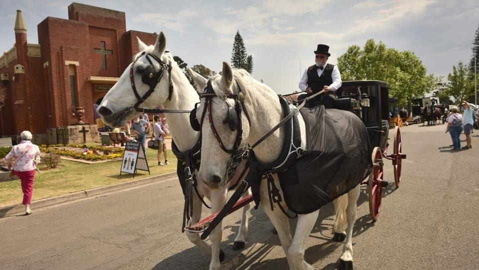 "A vintage horse-drawn hearse is driven past a mausoleum during an open day at Rookwood in Sydney. The cemeteries authority has also organised ""Death Over Dinner"" events --where guests share a meal and ask expert speakers about the end of life-- to normalise discussions around dying. (Peter Parks / AFP)"
