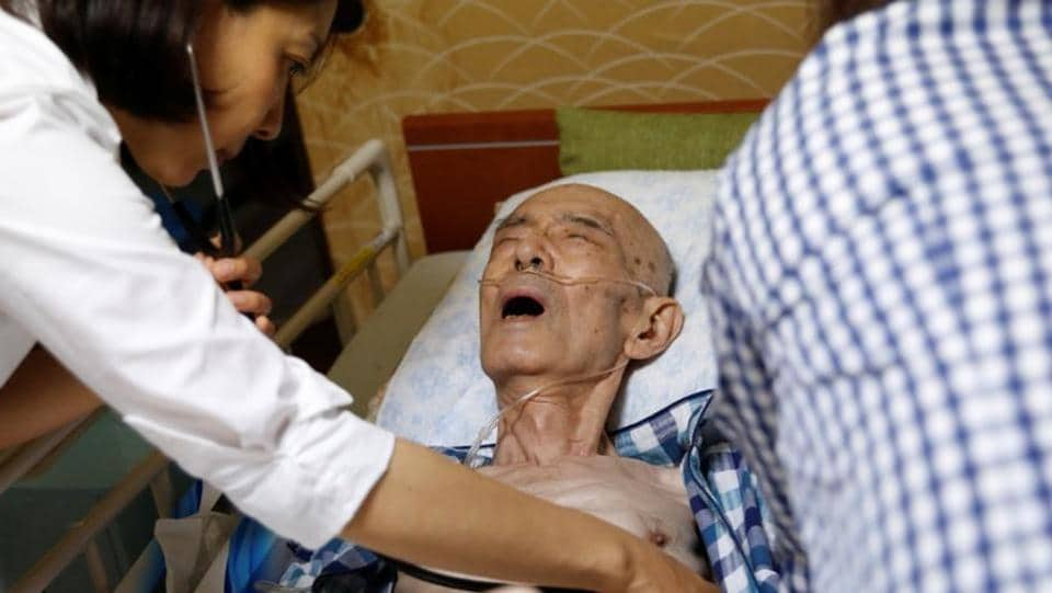 "Yamato Clinic's doctor Shima Onodera examines Yasuhiro Sato, who had terminal lung cancer, the day before his death at his house in Tokyo. ""It's okay. I'm not a burden to anybody,"" he said. ""I will go to the afterlife quietly. Alone."" (REUTERS)"
