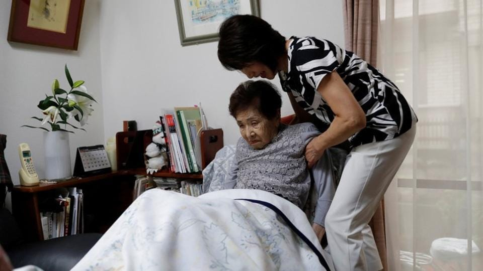 Yasuda Toyoko, 95, who has stomach cancer and dementia, is helped by her daughter, Terada. Terada said she decided to take care of her mother because she believed being in hospital weakened her and worsened her dementia. (Kim Kyung-Hoon / REUTERS)