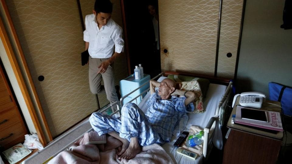 "Yuu Yasui, doctor and founder of Yamato Clinic, visits Yasuhiro Sato, at his house. ""I think it's good to have a doctor supporting people who choose to spend their final days and naturally face death in a place they spent their days living,"" said physician Yuu Yasui. (Kim Kyung-Hoon / REUTERS)"