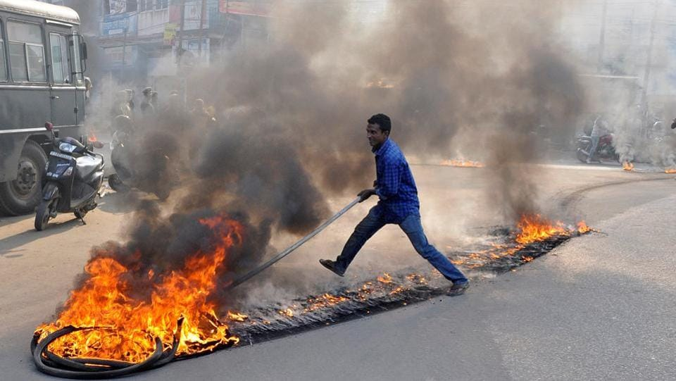 A demonstrator drags burning tires during a day-long strike to protest against the killing of Sudip Datta Bhowmik. Markets were closed and vehicles were off the roads in the state in view of the bandh. Schools, colleges, banks and financial institutions remained closed and attendance in government offices was also poor. (Jayanta Dey / REUTERS)