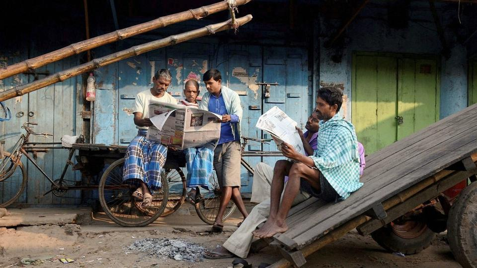 Daily wage workers read newspapers as a strike called by BJP and Congress party hit normal life in Agartala. Barring 'Daily Desher Katha', all other newspapers left their editorial columns blank today in protest against the killing. This is the second instance of a journalist being killed in the state in recent months. (PTI)
