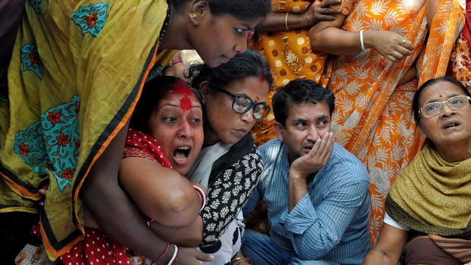Shima (in red) mourns next to the body of her husband Sudip Datta Bhowmik, 50, a local journalist who was allegedly shot by a Tripura State Rifles trooper on Tuesday, in Agartala. Various political parties called for a dawn-to-dusk shutdown, demanding a CBI inquiry and the resignation of chief minister Manik Sarkar. (Jayanta Dey / REUTERS)