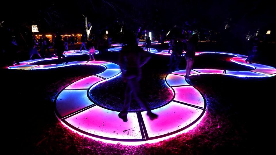 "In the exhibit's ""Luminous Lawn"", artist Jen Lewin's latest installation is a serpentine walkway that changes colour as visitors meander along. (Mario Anzuoni / REUTERS)"