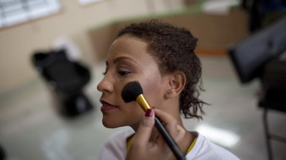 An inmate keeps still as an event volunteer applies her blush for the annual beauty contest. (Silvia Izquierdo / AP)