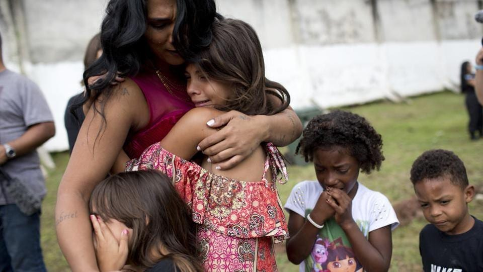 Female inmate Rossana Goncalves cries with her children by her side, as they reunite on the sidelines of competing in the pageant at Talavera Bruce prison in Rio de Janeiro. The three finalists won an electric fan, an iron and a fan respectively. (Silvia Izquierdo / AP)