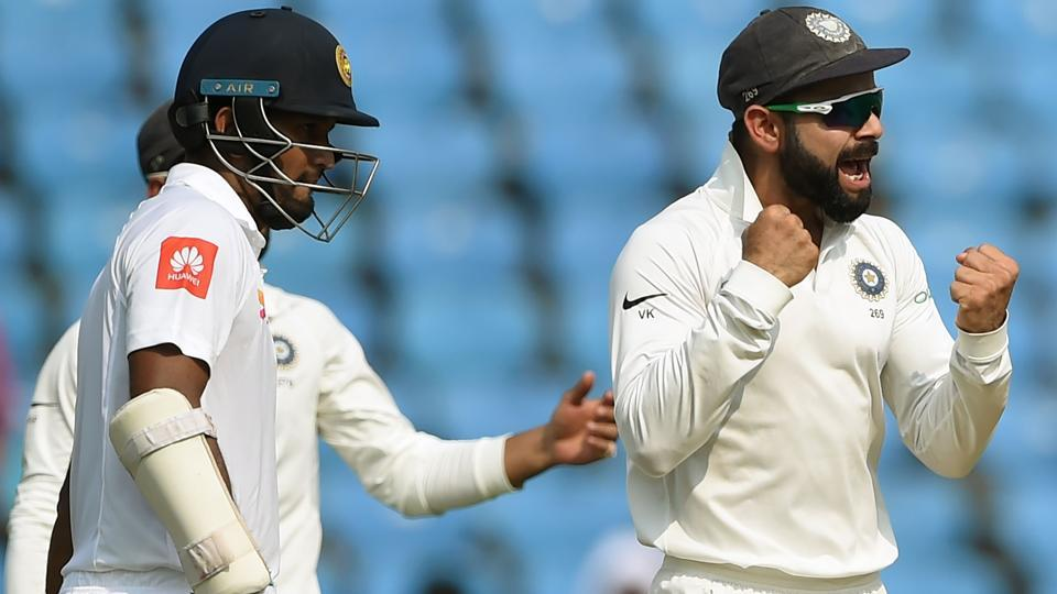 Indian cricket team captain Virat Kohli (R) celebrates after the wicket of Sri Lanka batsman Dimuth Karunaratne (L). (AFP)