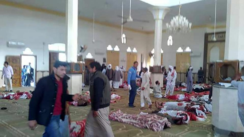 Egyptians walk past bodies following a gun and bombing attack at the Rawda mosque on Friday.