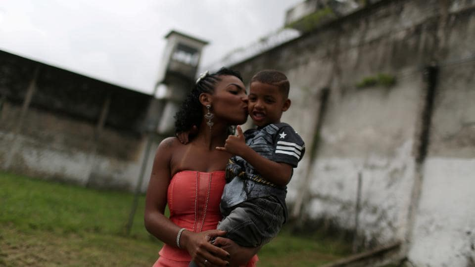 A participant of the 'TB Girl' beauty contest kisses her son at the Talavera Bruce women prison in Rio de Janeiro. (Pilar Olivares  / REUTERS)