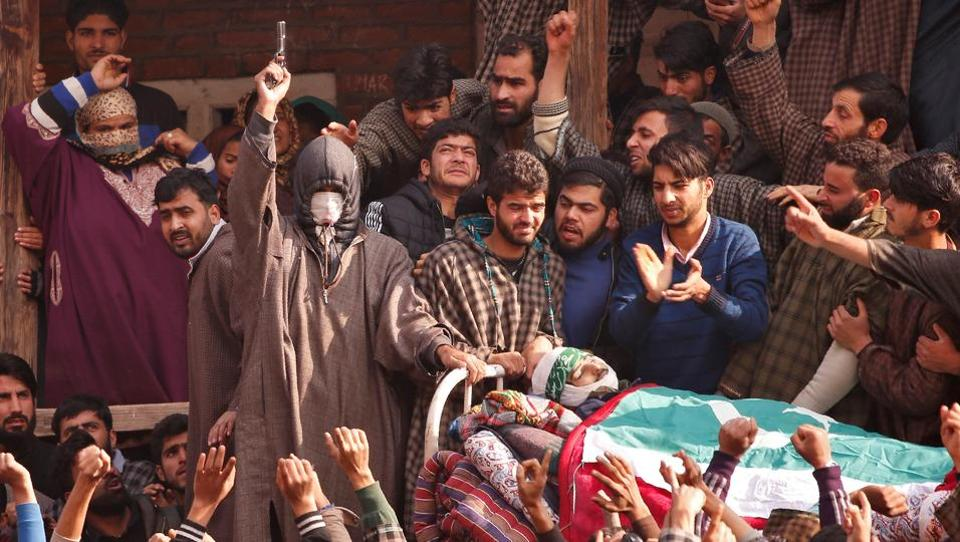 An unidentified man fires his pistol next to the body of Adil Rashid Chopan, a suspected militant, during his funeral procession at Lurrow village in Kashmir's Tral town on  November 21, 2017. (Danish Ismail  / REUTERS)