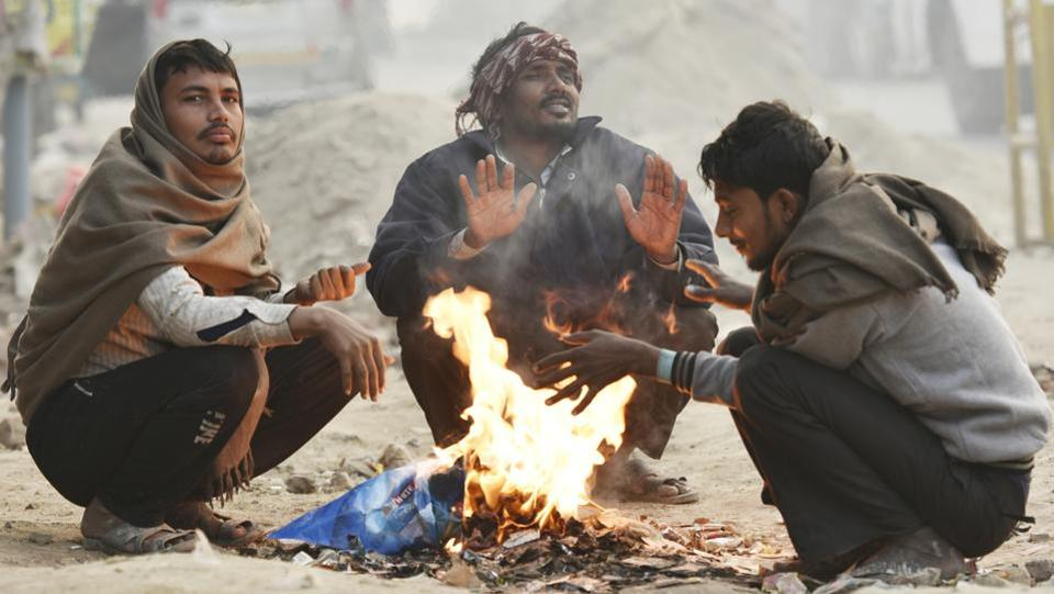 People warm themselves around a bonfire on a cold winter morning in New Delhi. To curb the practice of waste-burning during winter, Delhi environment minister Imran Hussain on Tuesday directed officials to ensure electric heaters are provided at all night shelters and to guards across government offices. (Raj K Raj / HT Photo)