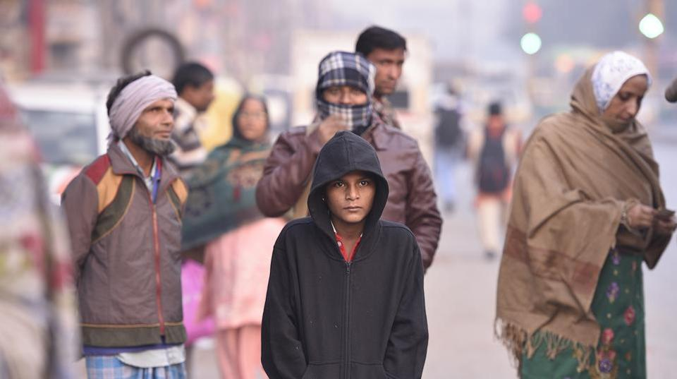 People gear up against a winter morning's chill as temperatures finally dip across North India. The change in weather is aided from winds making their way from Jammu and Kashmir and Himachal Pradesh which received snowfall over the past few days. (Raj K Raj / HT Photo)