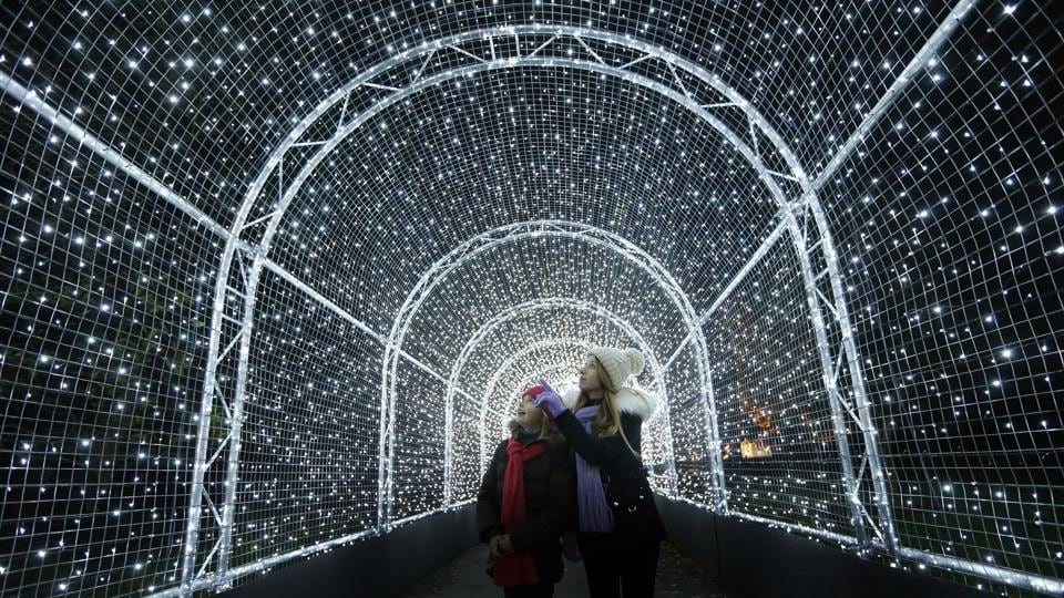 Visitors walk through a tunnel covered in lights, as part of a Christmas illuminated trail through Kew Gardens, in London on Tuesday. (Frank Augstein) / AP)