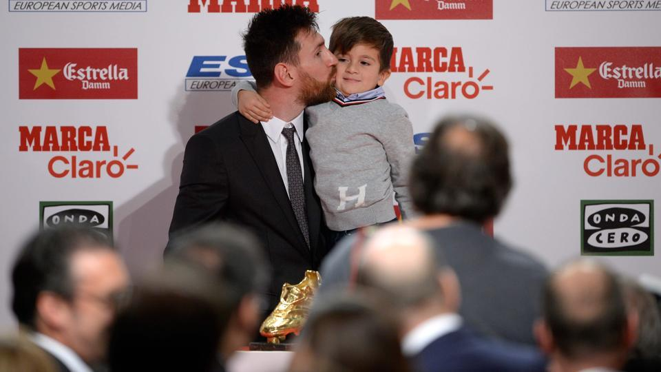 Lionel Messi kisses his son Thiago after receiving the 2017 European Golden Shoe award.  (AFP)