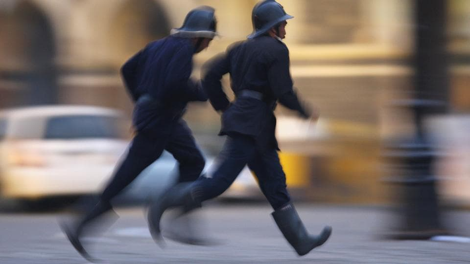 Policemen run for cover outside the Taj Mahal Palace & Tower Hotel during the armed siege, on November 28, 2008 in Mumbai. (Uriel Sinai / Getty Images)