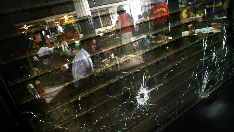 A man is reflected in a window with bullet holes at the Leopold Cafe after it reopened on December 2, 2008 in Mumbai, India. The Cafe was one of several locations targeted by multiple coordinated terrorist attacks on November 26. (Uriel Sinai / Getty Images)