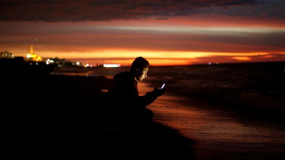 A Palestinian youth uses his mobile phone as he sits on a beach in the northern Gaza Strip November 24, 2017.