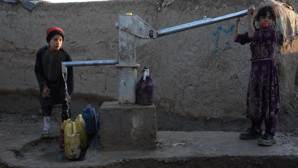 Internally displaced Afghan children fetch water from a pump at a refugee camp in Kabul on November 19, 2017. (Noorullah Shirzada / AFP)