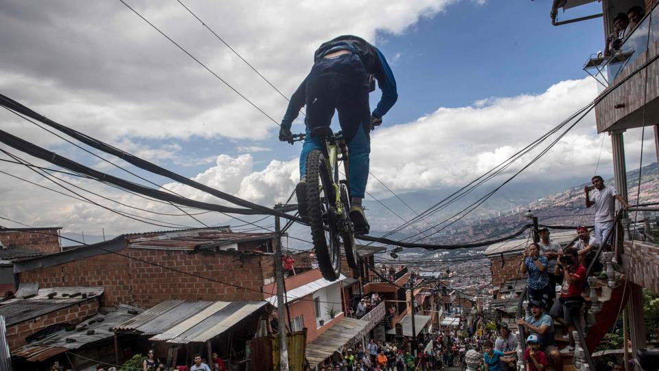 Residents watch as a downhill rider competes during the Urban Bike Inder Medellin race final at the Comuna 1 shantytown in Medellin, Colombia on November 19, 2017. (Joaquin Sarmiento / AFP)