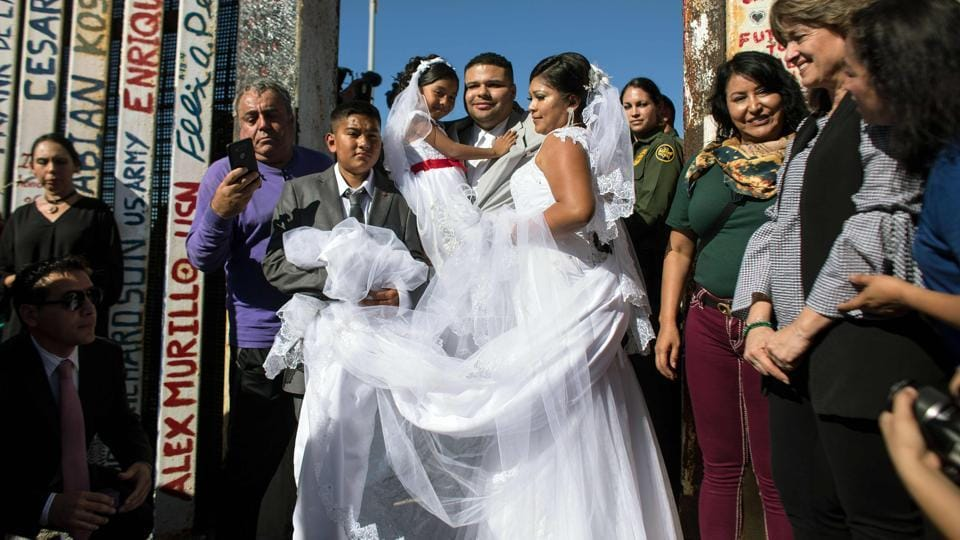 Bride Evelia Reyes and groom Brian Houston, living on different sides of the US-Mexico border, stand for a family portrait after getting married during a briefly reunited during the