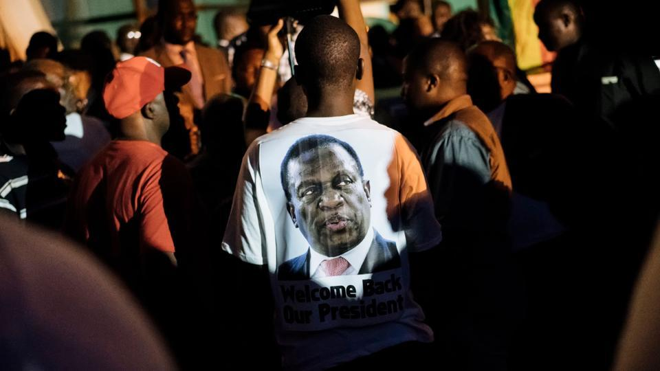 A supporter of Zimbabwe's incoming president Emmerson Mnangagwa wore a t-shirt with his portrait at Zimbabwe's ruling Zanu-PF party headquarters in Harare on November 22, 2017.  Zimbabwe's former vice president Emmerson Mnangagwa flew home on November 22 to take power after the resignation of Robert Mugabe put an end to 37 years of authoritarian rule. (Marco Longari / AFP)