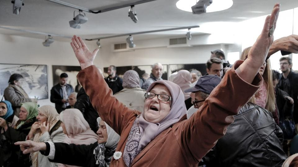 A Bosnian woman raises her arms upon hearing the sentence at the end of former Bosnian Serb military chief Gen. Ratko Mladic's trial at the memorial center in Potocari, near Srebrenica on Wednesday. (Amel Emric / AP)