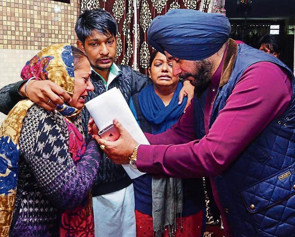 Punjab local bodies minister Navjot Singh Sidhu consoling deceased firefighter Sumohan Gill's wife Venus Gill (left), son Sahil Gill and daughter Shanaz Gill in Amritsar on Sunday.