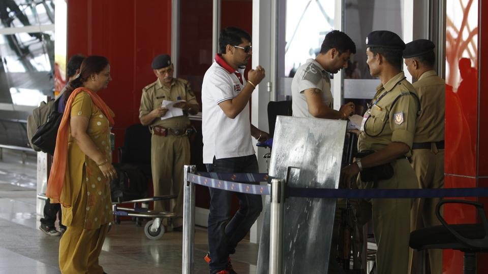 Passengers show their identity cards at the entrance to the airport.