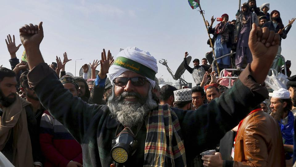 Supporters of the radical religious party Tehreek-e-Labbaik Pakistan celebrate after law minister Zahid Hamid's resignation during a sit-in protest in Islamabad on November 27, 2017. Pakistani Islamists announced they were disbanding their sit-in after the law minister resigned, caving in to the protesters who had been demanding his ouster in a three-week-long rally.
