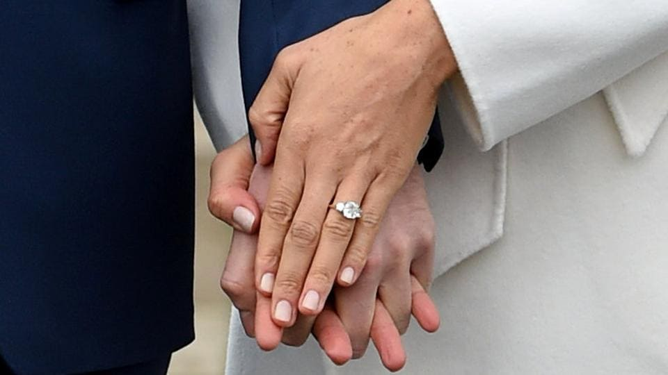Meghan Markle's engagement ring sparkles as she poses with Prince Harry in the Sunken Garden of Kensington Palace on November 27, 2017 in London, Britain. Harry and Markle, who is a divorcee, met in July 2016 after they were introduced through friends. (Eddie Mulholland / Pool / REUTERS)