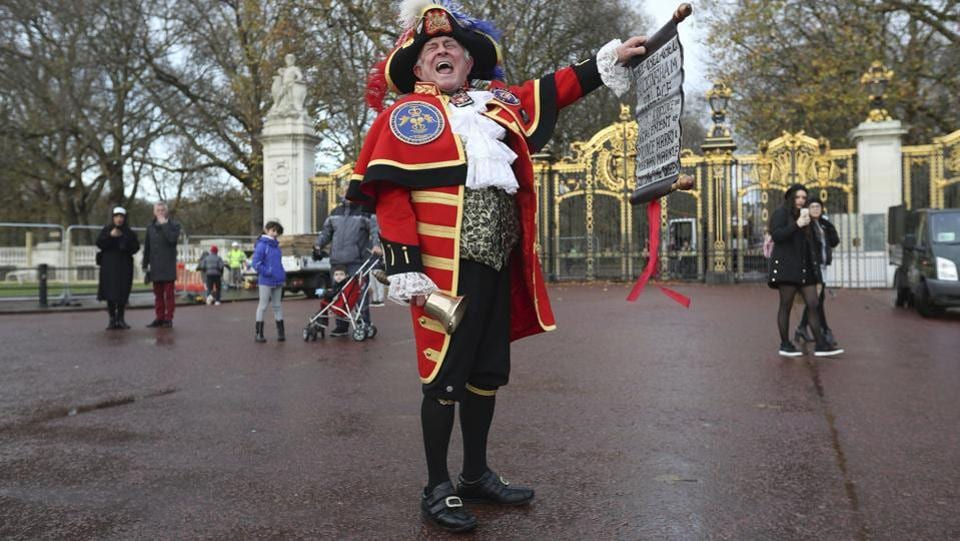 Town Crier Tony Appleton shouts as he holds a scroll outside Green Park in central London near Buckingham Palace after it was announced that Prince Harry and Meghan Markle were engaged. (Jonathan Brady / AP)