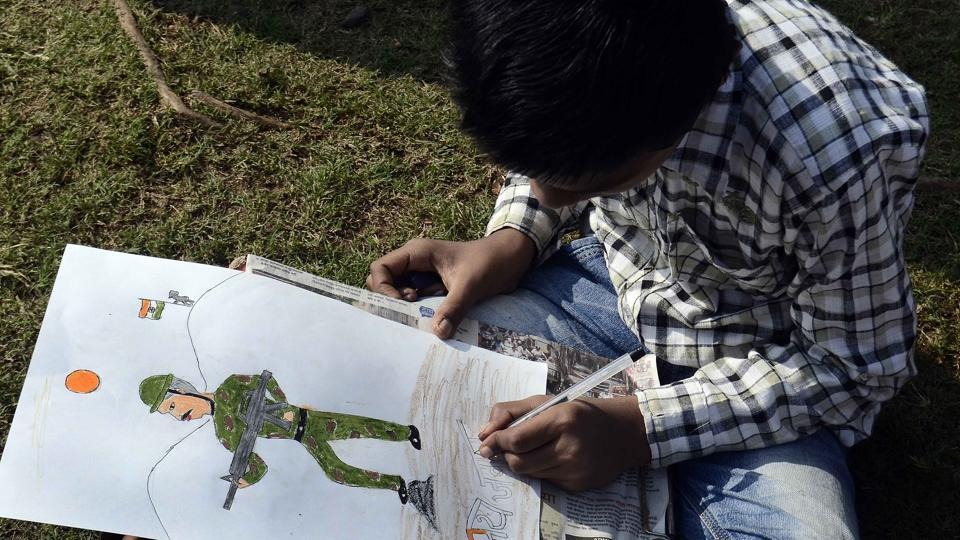 A boy doing some finishing touches to his painting of a soldier who fought for the nation during the 26/11 attacks. (Ravindra Joshi/HT PHOTO)