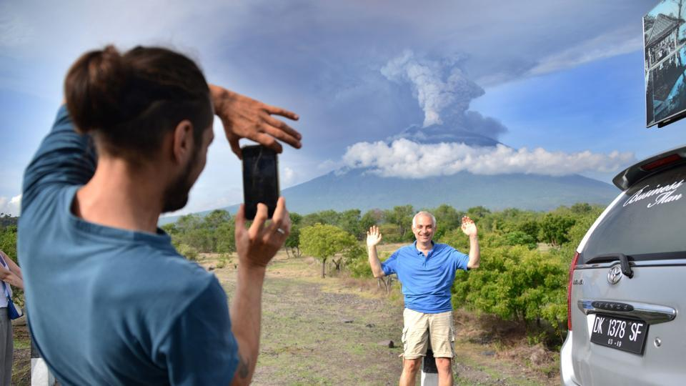 A tourist takes pictures in front of Mount Agung on November 27, 2017. An eruption could be imminent as the volcano belches huge plumes of smoke, officials warned. Spokesman Sutopo Purwo Nugroho said about 40,000 people have evacuated but others have not left because they feel safe or don't want to abandon their livestock. (Sonny Tumbelaka / AFP)