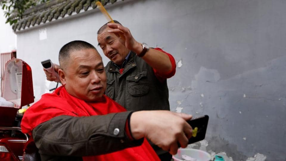"A customer takes a selfie with Xiong Gaowu (R) midway a trim in Chengdu. Customers swear by the practice of ""blade wash eyes"", as it is known in Mandarin, saying they trust Xiong's skill with the blade. Xiong learned the technique in the 1980s and serves up to eight customers a week, charging 80 yuan ($12) per shave. (Tyrone Siu / REUTERS)"
