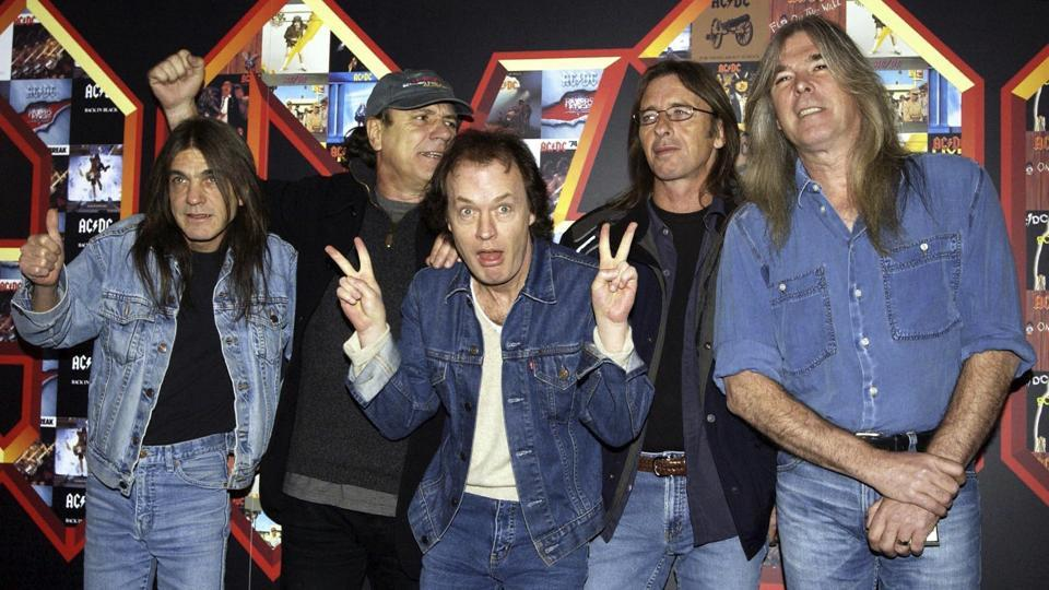 Malcolm Young, Brian Johnson, Angus Young, Phil Rudd and Cliff Williams from AC/DC pose for photographers at the Apollo Hammersmith in London, 2003. Young founded the group with Angus in 1973, and was a driving force in making it one of the biggest rocks acts in the world. (Yui Mok / AP)
