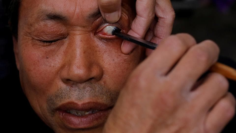 A customer looks on as Xiong Gaowu, a street barber cleans his eye using a straight razor in Chengdu, China. At his roadside location, 62-year-old Xiong provides along with the barber's classics of a trim and a shave, a wincingly close scrape right along the eyelids that few, if any hairdressers can offer --should a customer be brave enough to ask for it. (Tyrone Siu / REUTERS)