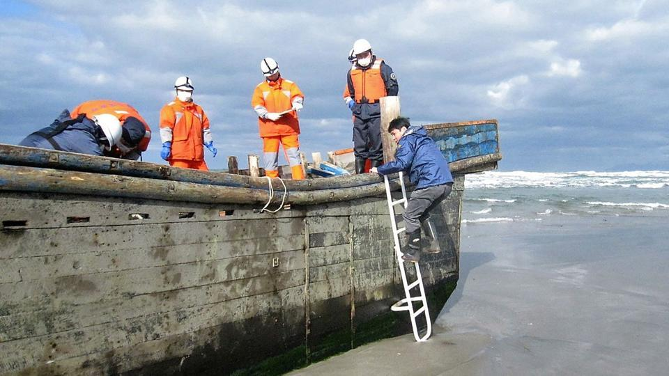 This handout picture taken on November 27, 2017 by the Oga city municipal office and released via Jiji Press shows coast guard officers inspecting a battered wooden boat where eight bodies were found inside at a beach in Oga, Japan's Akita prefecture.
