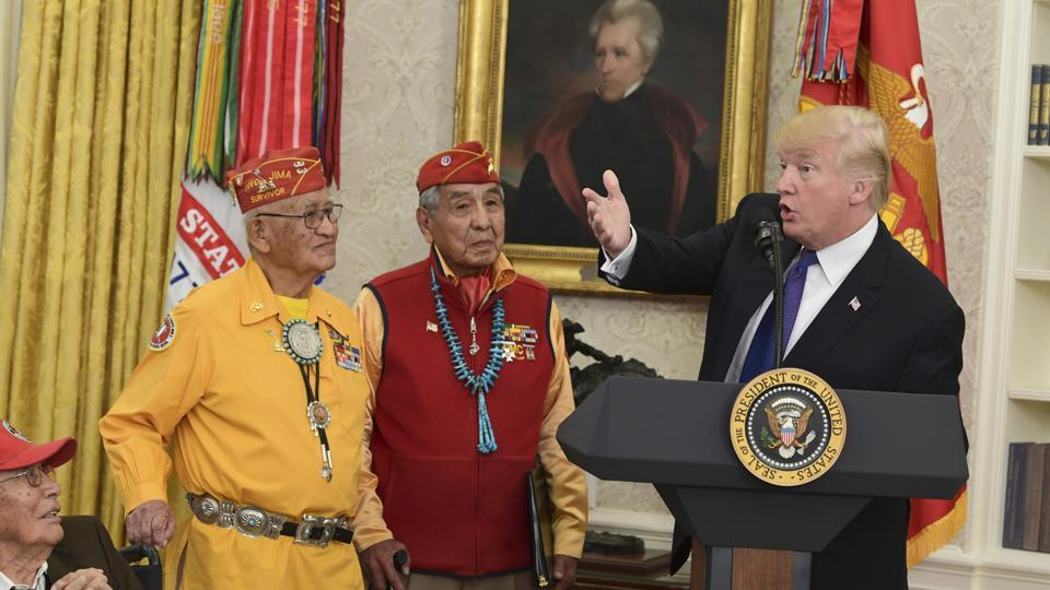 President Donald Trump (right)speaks during a meeting with Navajo Code Talkers including Fleming Begaye Sr. (seated left), Thomas Begay (second from left), and Peter MacDonald (second from right), in the Oval Office of the White House in Washington, on November 27, 2017.