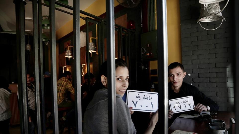 Customer Amr El Gohary, right, and his friend pose for a photograph with plastic plaques that translate to inmates with numbers, as they wait for their food, at prison-themed restaurant 'Food Crime' in the Nile Delta city of Mansoura, 110 kilometers (70 miles) north of Cairo, Egypt.