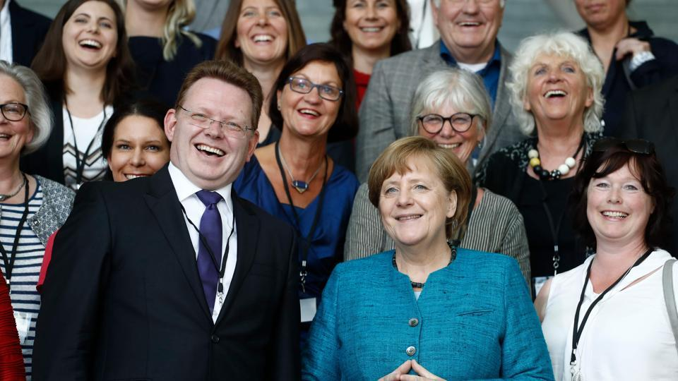 This file photo taken on May 17, 2017 shows German Chancellor Angela Merkel (right) posing with Altena's mayor Andreas Hollstein (left) and other winners of the national integration award at the Chancellery in Berlin. A knife attacker injured Hollstein in an assault which officials said appeared motivated by the municipal leader's pro-refugee stance.