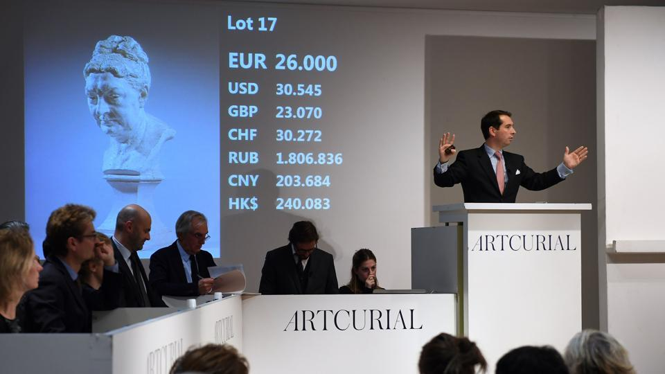 Auctioneer Matthieu Fournier (R) calls the sale at 26,000 euros for the sculpture depicting Camille Claudel's mother during an auction of artworks by French artist Camille Claudel at the Artcurial auction house in Paris, on November 27, 2017.