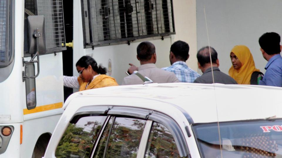 Hadiya (second from right in a yellow scarf) being escorted on her arrival at the Coimbatore airport on Tuesday.