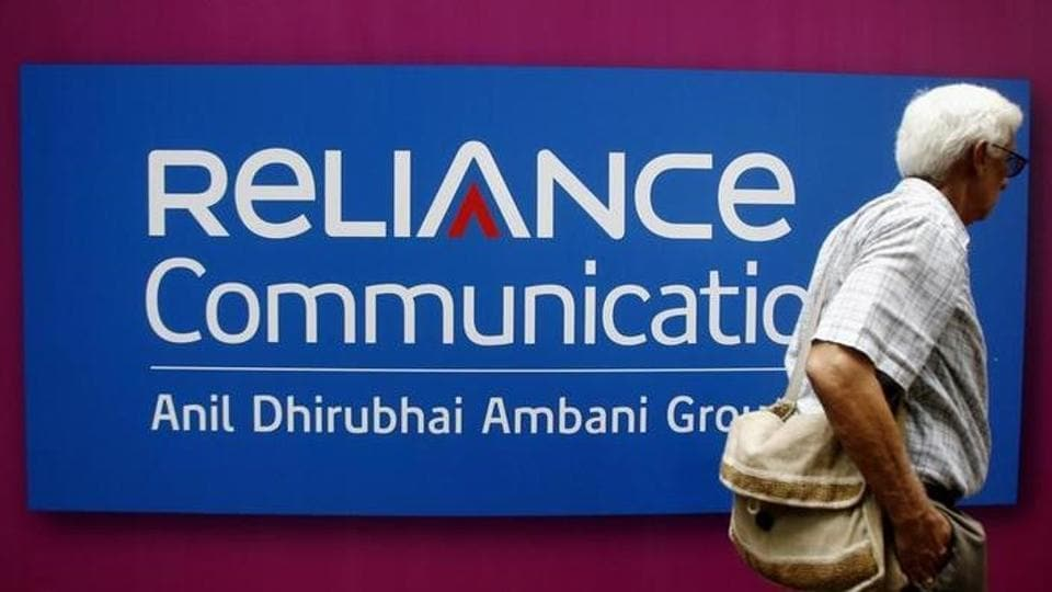 A man walks past a logo of Reliance Communication before the Annual General Meeting in Mumbai September 22, 2009.