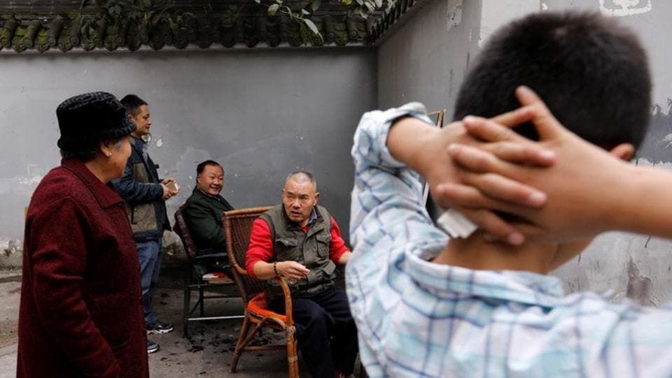 Xiong Gaowu (C), engages with customers during a break on a workday. When Xiong runs his razor, it is most likely that he shaves the openings of the sebaceous glands which cause discomfort and dryness in the eye when they are blocked, hence the demand for this technique, Qu theorised. (Tyrone Siu / REUTERS)