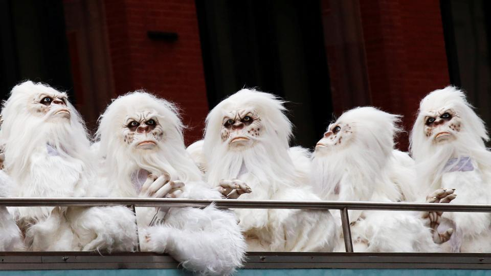 Actors dressed as a 'Yeti' ride aboard a tour bus during a promotional event for Travel Channel's