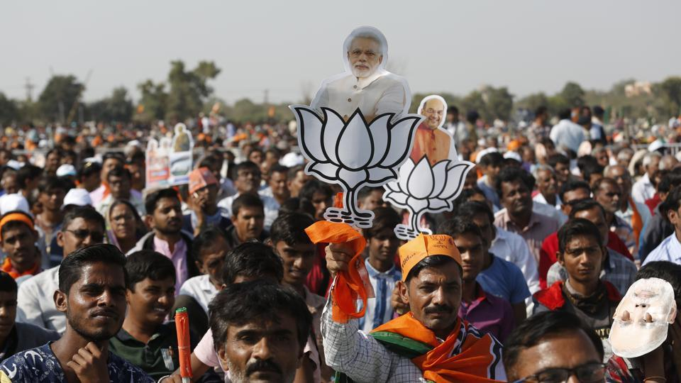 Supporters of the BJP hold party symbols with photographs of PMNarendra Modi, centre, and party president Amit Shah during an election campaign rally at Morbi in Gujarat on Wednesday.