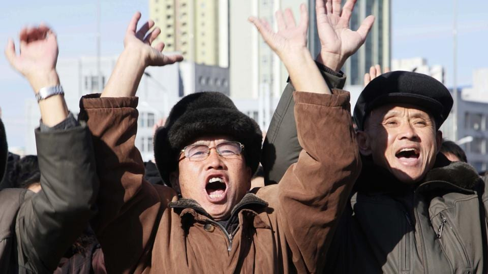 People cheer as they watch a news broadcast at the Pyongyang Train Station announcing North Korean leader Kim Jong Un's order to test-fire missile Hwasong-15 on Wednesday. Pyongyang said the missile reached an altitude of 4,475 kilometres (2,800 miles) and splashed down 950 kilometres from its launch site. (Jon Chol Jin / AP)