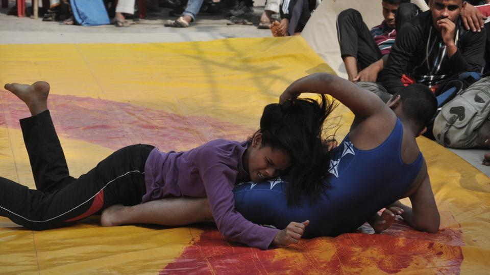 "Karan and Khushi Yadav grapple during their match in the competition. From a family of wrestlers, the siblings are trained by their grandfather Kallu Pahalwan. ""My father (Vinod Yadav) had participated in national wrestling championships. I want to be an international wrestler. Winning gold for the country in the Olympics is my dream,"" Khushi said after besting her brother. (Rajesh Kumar / HT Photo)"
